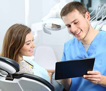 Best Cosmetic Dentists in Charleston - A denist is shwowing about dental instruments to a patient