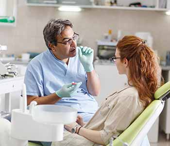 FAQs on Veneers Charleston - Dentist is describing about veeners to a patient